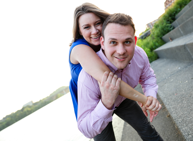 A man in a pink shirt carries a young woman in a blue dress on his back. She is laughing. engagement photography