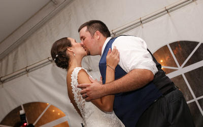 Wedding photography, a bride and groom kiss lovingly.