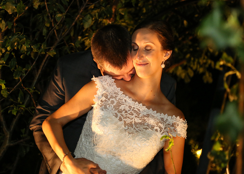 Wedding photography, a groom kisses his bride's neck, she smiles serenely.