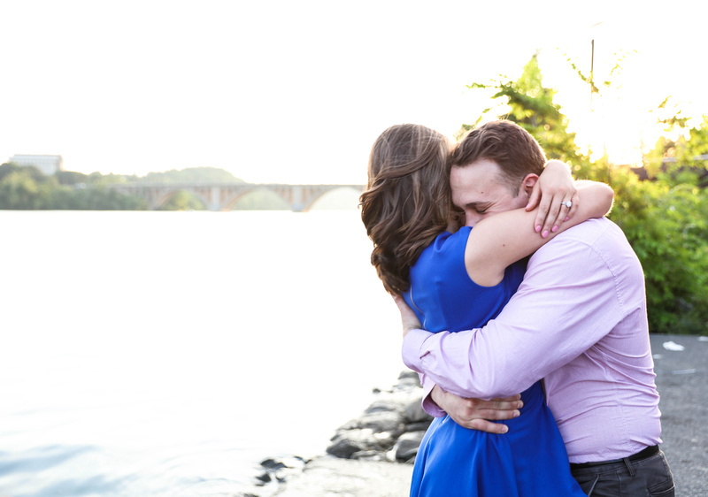 A young couple passionately embraces each other by the waterfront. She is wearing an engagement ring.