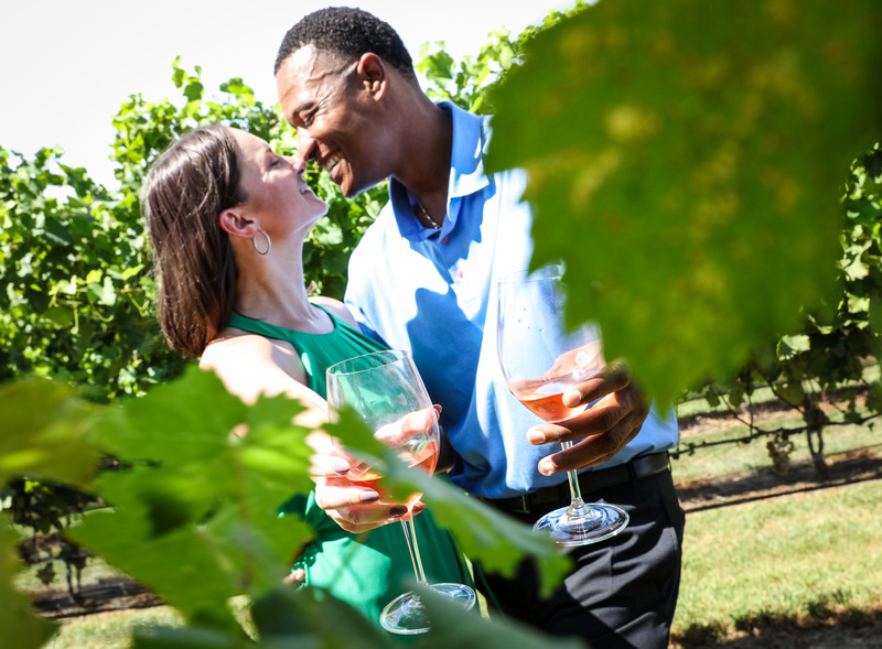 Engagement photography: a couple puts their noses together and laughs while toasting white wine at a vineyard.