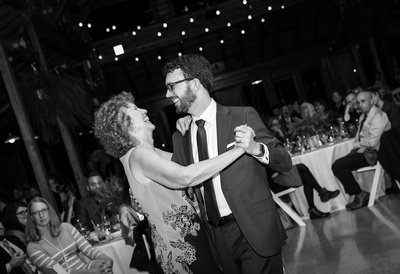 Wedding photography, a groom laughs while dancing with his mother.