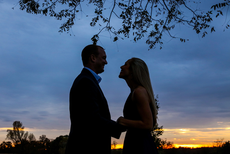 The silhouette of a young couple at sunset. They are holding hands and smiling at each other.