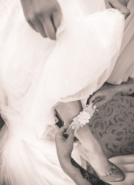 Wedding photography, a closeup of a garter being slipped onto the leg of a bride.
