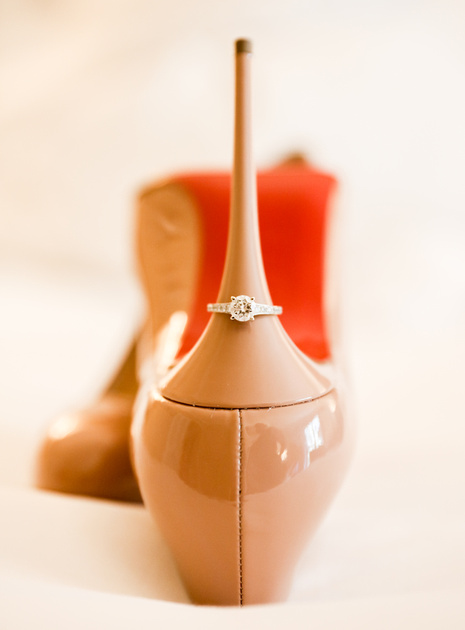 Wedding photography, a pair of nude high heels with a red bottom on a bed. On the heel is a diamond engagement ring.