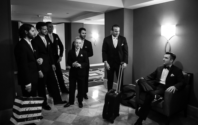 Wedding photography, a dark haired groom in a black tuxedo sits confidently in a chair while his groomsmen stand nearby smiling.