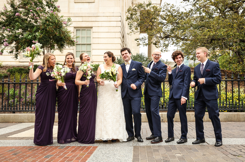 Wedding photography, a wedding party with bridesmaids in long purple gowns and groomsmen in navy blue suits.