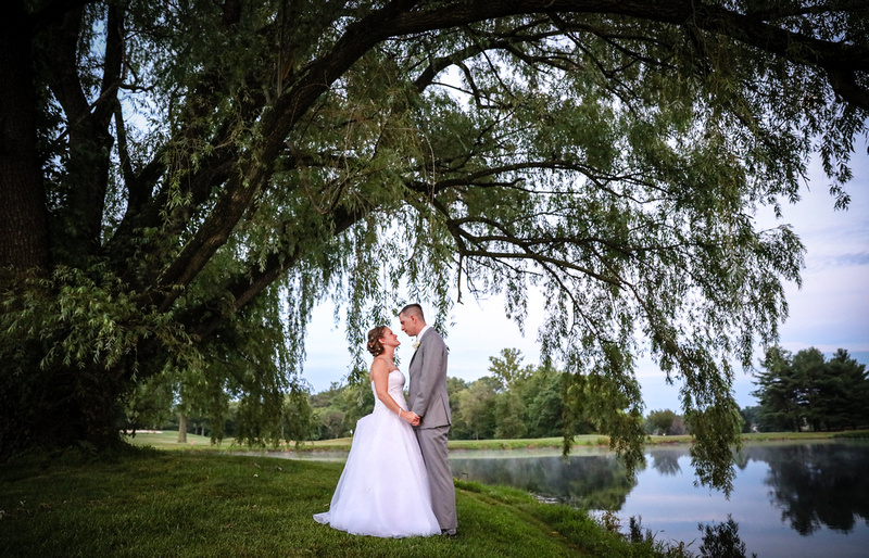 Wedding photography, a bride and groom gaze at each other beneath a large tree next to a pond.