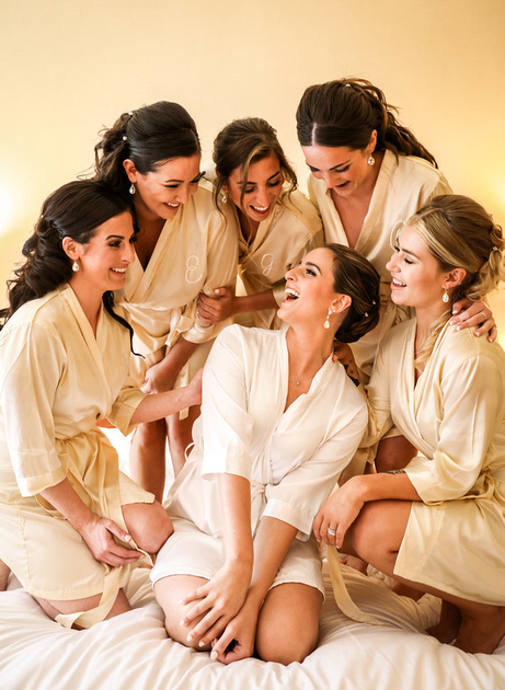 Wedding photography, a bride and her bridesmaids huddle together in their robes laughing.