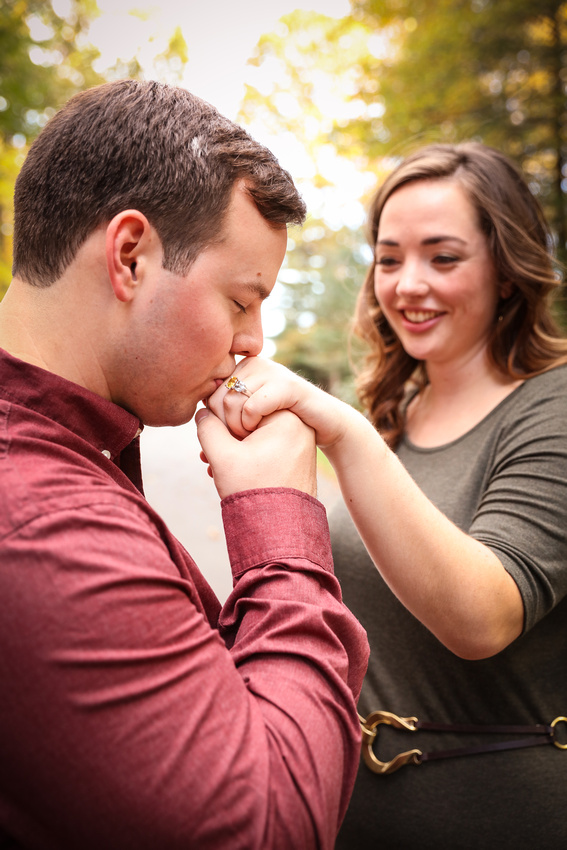 Engagement photography: a young man kisses his fiancé's hand while she smiles.