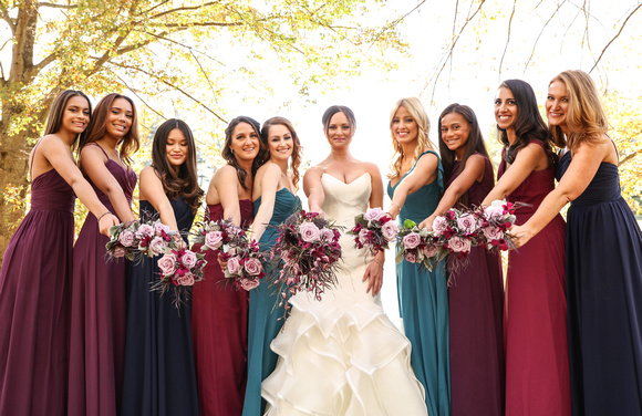 Wedding photography, the bride and bridesmaids stand together in front of yellow trees, holding out their purple bouquets.