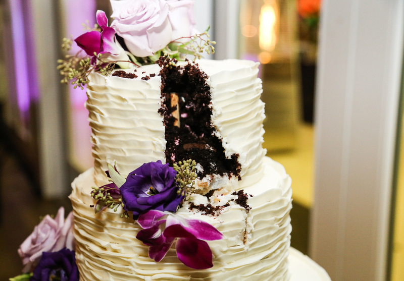 Wedding photography, a slice cut out of a chocolate cake with vanilla frosting and purple flowers.