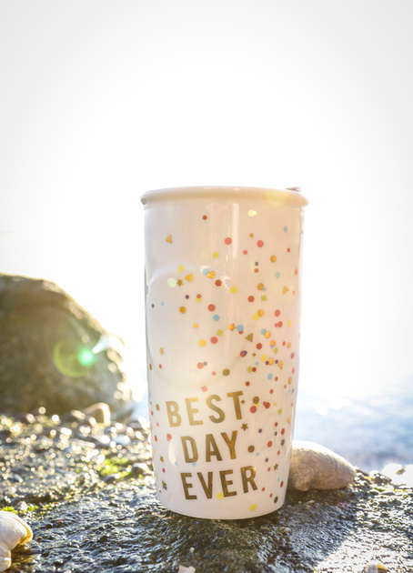 "Wedding photography, a mug that says ""Best Day Ever"" sits on a rock by the water."