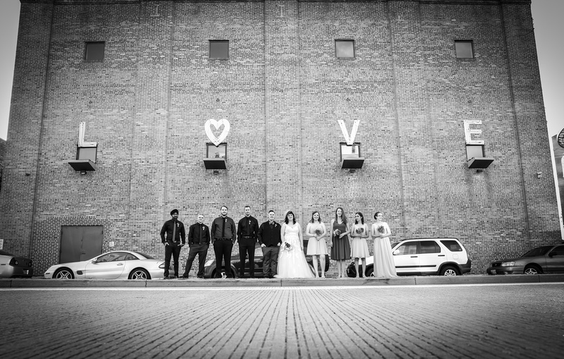 Wedding photography, black and white image of a wedding party standing on the street in front a brick building that spells out LOVE.