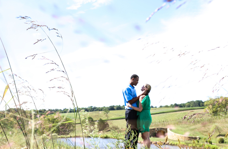 Engagement photography: a couple embraces while standing in an open field at a vineyard.
