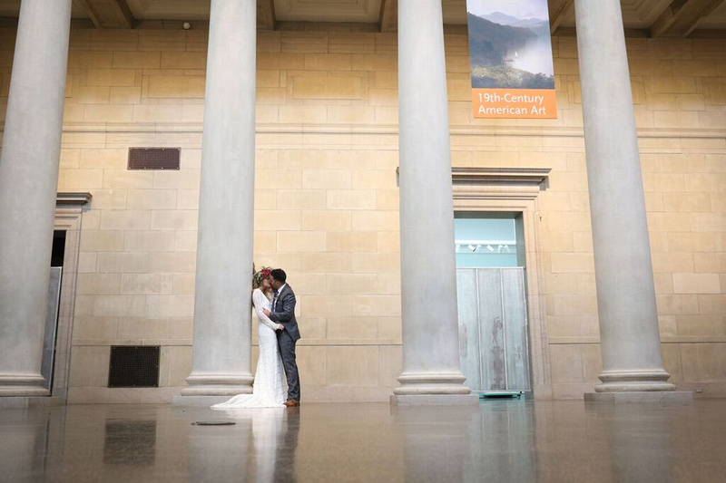 Bride and groom kiss as bride leans against a giant while marble column in a large open gallery at the baltimore museum of art. Styled wedding shoot by photos by kintz