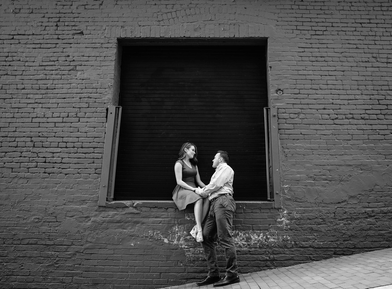 Young woman sits on a brick wall. She rests her hand in her fiancé's, who looks up at her. engagement photography