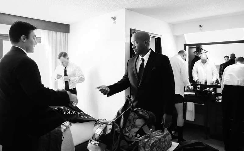 Wedding photography, a groom and his groomsmen get dressed in their hotel room.