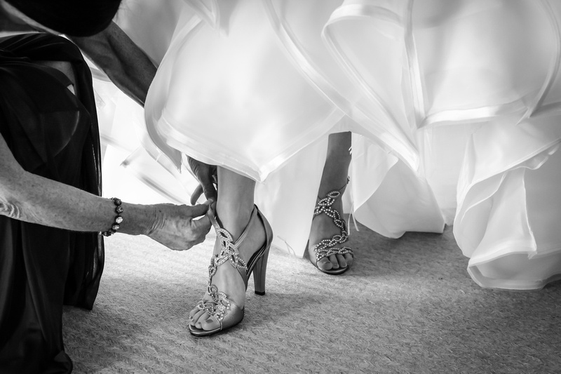 Wedding photography, a black and white image of a bride's feet as her mother puts on her high-heeled diamond shoes.