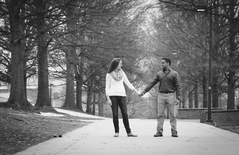 Engagement photography, a couple holds hands and looks at each other in a tree-lined pathway.