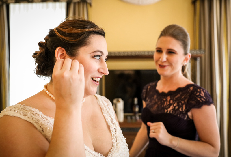 Wedding photography, a bride in a lace gown smiles while putting on her earrings.
