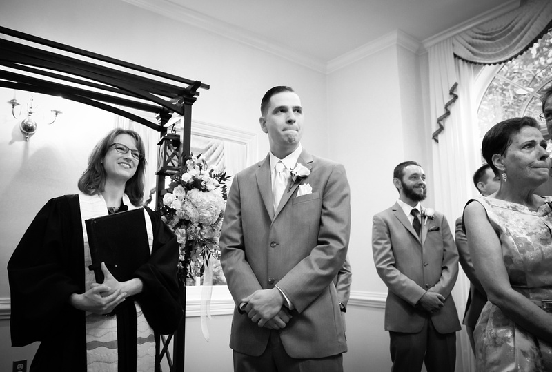 Wedding photography, an emotional groom watches his bride walk down the aisle.