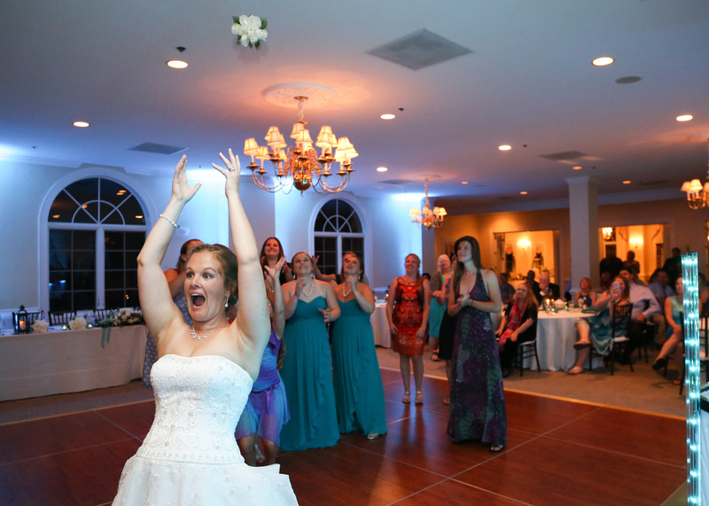 Wedding photography, a bride throws her bouquet into a crowd of women, eager to catch it.