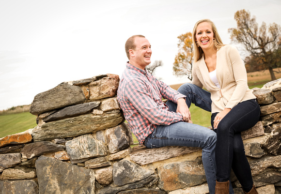 Engagement photography, a couple laughs out loud while sitting on a stone wall.