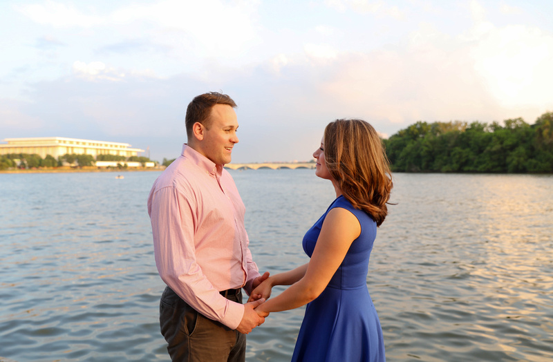 A couple stands holding hands and facing each other. They are by the waterfront and smiling lovingly. engagement photography