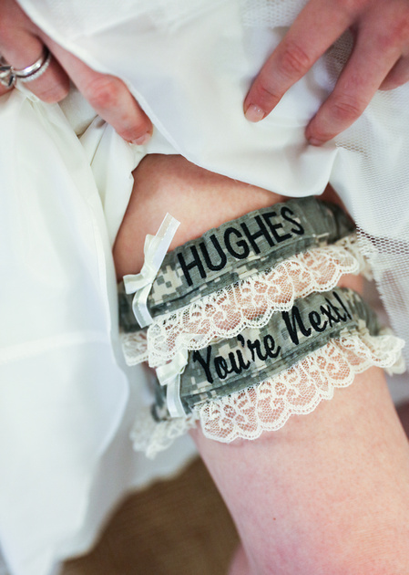 Wedding photography, a bride pulls up her dress to show two garters on her right leg.