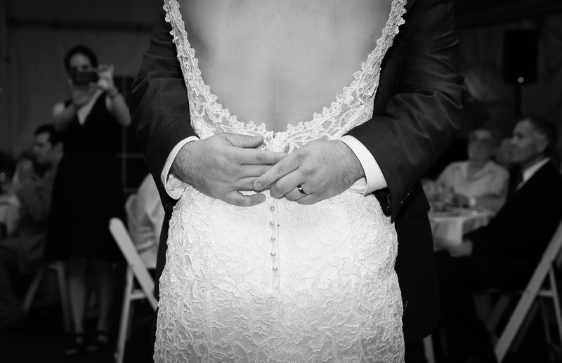 Wedding photography, a closeup shot of a groom's hands wrapped around a bride's back. She wear a low back lace gown.