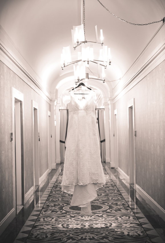 Wedding photography, a wedding gown hangs from a chandelier in a hotel hallway.