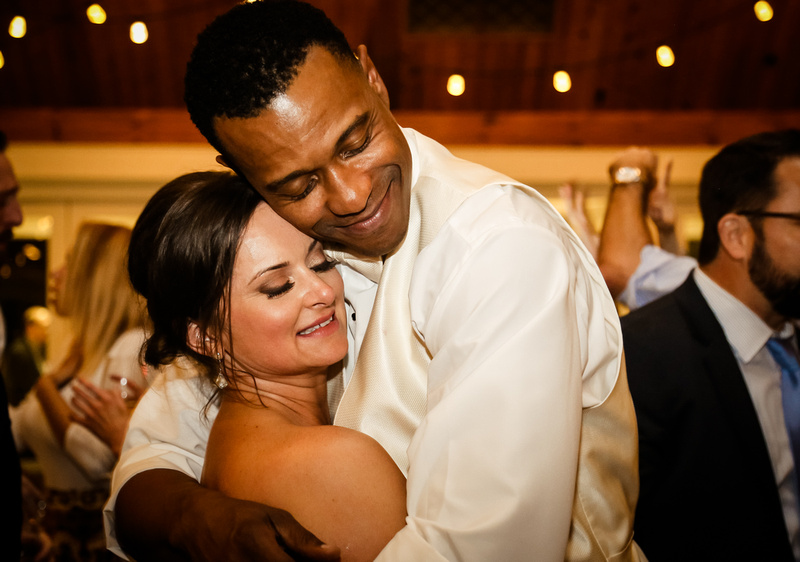 Wedding photography, the bride and groom embrace and smile with their eyes closed, while slow dancing on the floor.