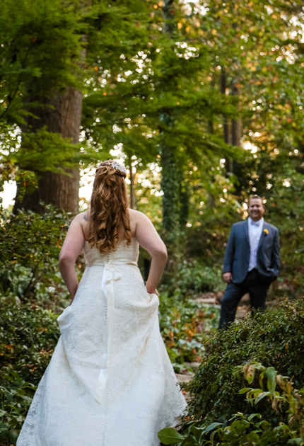 Wedding photography, the bride holds up her dress and walks through the forest to meet her groom.