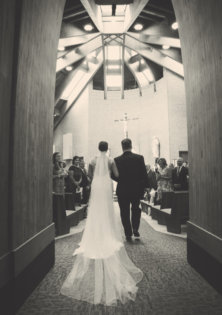 Wedding photography, a bride and her father walk down the aisle of a church. Her veil drapes down her back and trails on the floor.