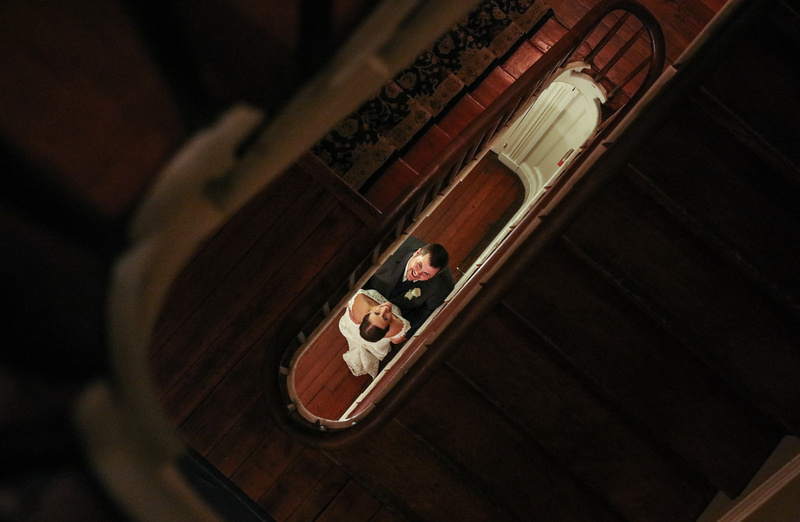 Wedding photography, looking down a spiral stairwell you see a bride and groom looking up at the camera, smiling.