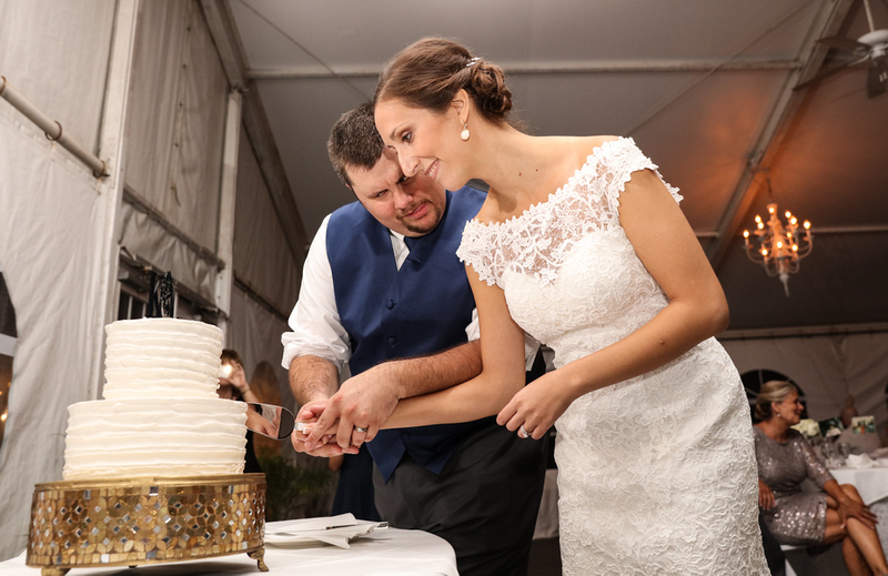 Wedding photography, a bride and groom cut their white cake which sits on a gold stand. He is focused and sticking out his tongue. She is smiling.