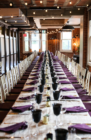 Wedding photography, a long dinner table set with purple napkins and navy blue goblets.
