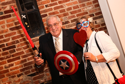 Wedding photography, an older couple has fun with some props at the photo booth.