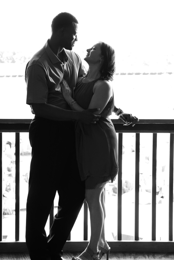 Engagement photography: a black and white photo of a couple leaning on a railing in a loving embrace.