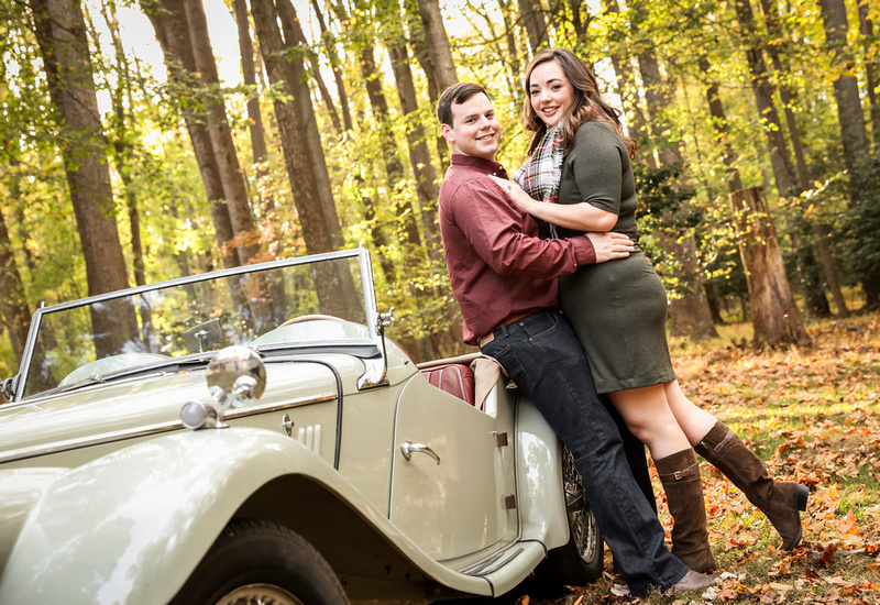 Engagement photography: two fiancées lean against an antique car and smile.