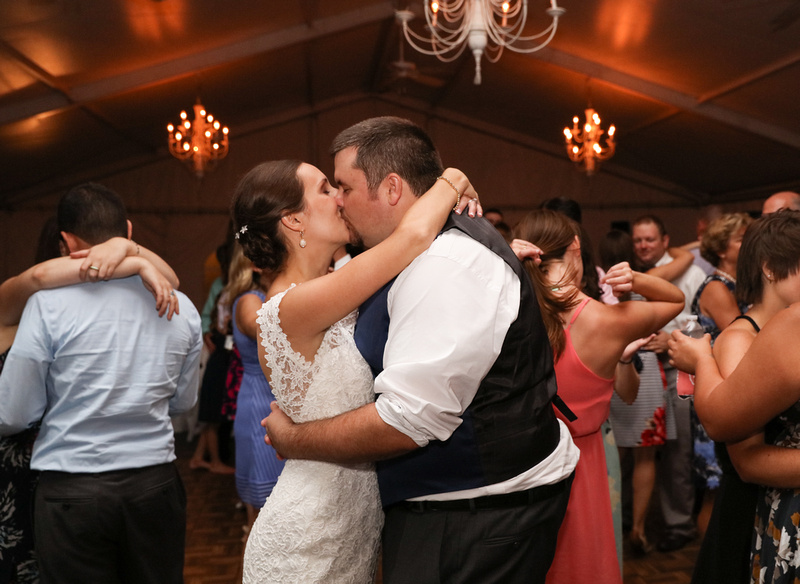 Wedding photography, a bride and groom kiss passionately on the dance floor. Their friends dance behind them.