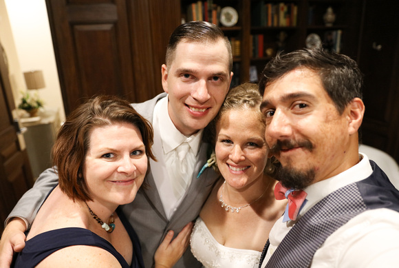Wedding photography, a bride and groom cuddle up with their happy wedding photographers.