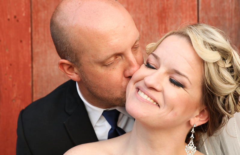 Wedding photography, the bride smiles serenely as her husband kisses her cheek.