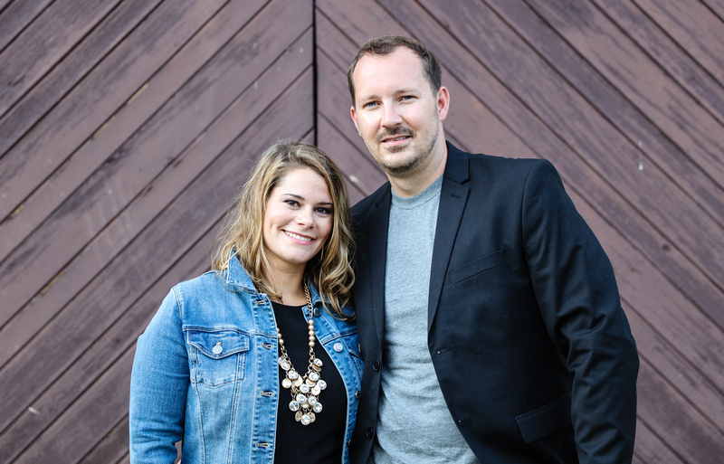Family photography: a couple stands in front of brown barn doors. She wears a jean jacket with a gold necklace. We wears a black blazer.