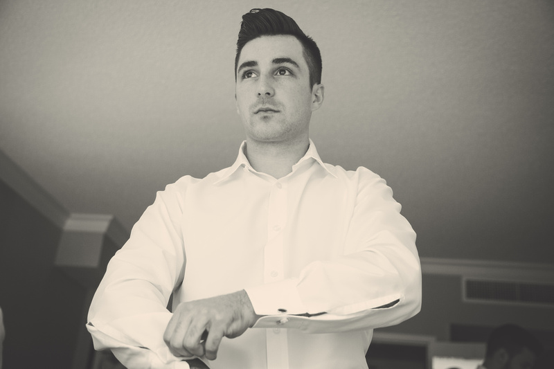 Wedding photography, a handsome young man putting on a white dress shirt.