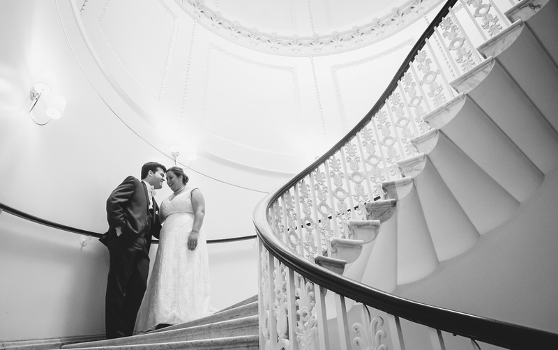 Wedding photography, a bride and groom put their foreheads together on a grand staircase.