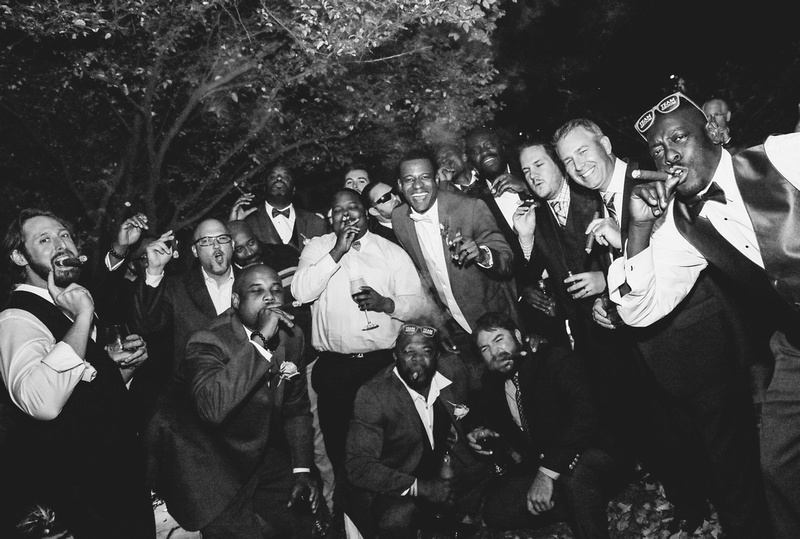 Wedding photography, a black and white image of a big group laughing while smoking cigars under a tree.