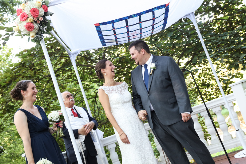 Wedding photography, the bride and groom smile at each other. They stand under a white huppa with pink flowers on the top.