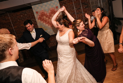 Wedding photography, a bride and her bridesmaid link arms and twirl on the dance floor.